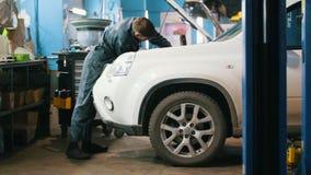 Μηχανικός στην υπηρεσία αυτοκινήτων - που επισκευάζει για άσπρο SUV απόθεμα βίντεο