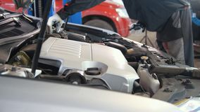 Μηχανικός στο γκαράζ αυτοκινήτων που ελέγχει την κουκούλα της πολυτέλειας sportcar Στοκ Φωτογραφία