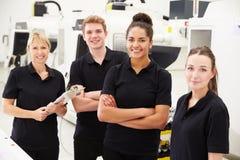 Μηχανικός στο εργοστάσιο με τους μαθητευόμενους που ελέγχουν τα συστατικά Στοκ Φωτογραφίες