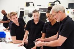 Μηχανικός στο εργοστάσιο με τους μαθητευόμενους που ελέγχουν τα συστατικά Στοκ εικόνα με δικαίωμα ελεύθερης χρήσης