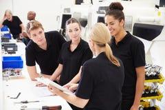 Μηχανικός στο εργοστάσιο με τους μαθητευόμενους που ελέγχουν τα συστατικά Στοκ φωτογραφία με δικαίωμα ελεύθερης χρήσης