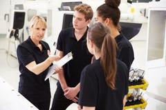 Μηχανικός στο εργοστάσιο με τους μαθητευόμενους που ελέγχουν τα συστατικά Στοκ Εικόνα
