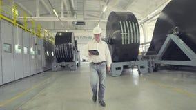 Μηχανικός στο σκληρό καπέλο που περπατά μέσω του εργοστασίου απόθεμα βίντεο