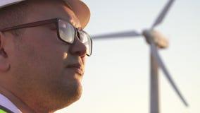 Μηχανικός της ασιατικής εμφάνισης με το κράνος που στέκεται στο φως του ήλιου και που ωθεί επάνω τα γυαλιά του απόθεμα βίντεο