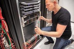 Μηχανικός ΤΠ που εργάζεται με τον κεντρικό υπολογιστή σε Datacenter στοκ εικόνα
