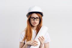 Μηχανικός-υπεύθυνος για την ανάπτυξη επιχειρησιακών γυναικών σε ένα κράνος με τα σχεδιαγράμματα σε ένα ελαφρύ υπόβαθρο Στοκ εικόνες με δικαίωμα ελεύθερης χρήσης