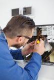 Μηχανικός υπολογιστών που εργάζεται στη σπασμένη κονσόλα με το κατσαβίδι Στοκ Εικόνα
