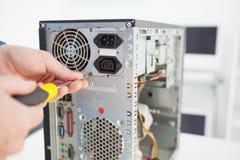 Μηχανικός υπολογιστών που εργάζεται στη σπασμένη κονσόλα με το κατσαβίδι Στοκ Φωτογραφίες