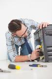 Μηχανικός υπολογιστών που εργάζεται στη σπασμένη κονσόλα με το κατσαβίδι Στοκ φωτογραφία με δικαίωμα ελεύθερης χρήσης