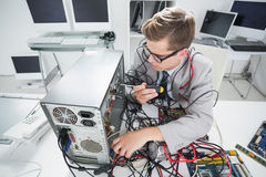 Μηχανικός υπολογιστών που εργάζεται στη σπασμένη κονσόλα με το κατσαβίδι Στοκ Εικόνες