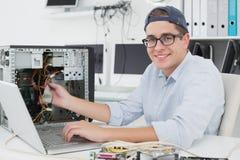 Μηχανικός υπολογιστών που εργάζεται στη σπασμένη κονσόλα με το lap-top Στοκ φωτογραφία με δικαίωμα ελεύθερης χρήσης