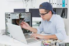 Μηχανικός υπολογιστών που εργάζεται στη σπασμένη κονσόλα με το lap-top Στοκ Εικόνες