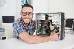 Μηχανικός υπολογιστών που εργάζεται στη σπασμένη κονσόλα που χαμογελά στη κάμερα Στοκ φωτογραφία με δικαίωμα ελεύθερης χρήσης