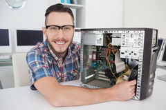 Μηχανικός υπολογιστών που εργάζεται στη σπασμένη κονσόλα που χαμογελά στη κάμερα Στοκ Φωτογραφία