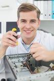 Μηχανικός υπολογιστών που εργάζεται στη σπασμένη συσκευή με το κατσαβίδι Στοκ εικόνα με δικαίωμα ελεύθερης χρήσης