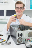 Μηχανικός υπολογιστών που εργάζεται στη σπασμένη συσκευή με το κατσαβίδι Στοκ Εικόνα