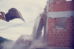 Μηχανικός digger που κατεδαφίζει τον τοίχο ενός κτηρίου τούβλου Στοκ φωτογραφία με δικαίωμα ελεύθερης χρήσης