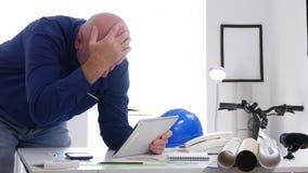 Μηχανικός gesticulate που απογοητεύεται μετά από να διαβάσει τις κακές ειδήσεις στην ταμπλέτα φιλμ μικρού μήκους
