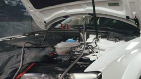 Μηχανικό άτομο που μετρά την τάση στην μπαταρία αυτοκινήτων στην αυτόματη υπηρεσία Συντήρηση αυτοκινήτων απόθεμα βίντεο