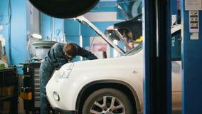 Μηχανικό αρσενικό στο αυτοκινητικό γκαράζ που ελέγχει την κουκούλα ενός αυτοκινήτου απόθεμα βίντεο