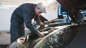 Μηχανικό αρσενικό στο αυτοκινητικό γκαράζ που ελέγχει την κουκούλα της πολυτέλειας sportcar Στοκ εικόνες με δικαίωμα ελεύθερης χρήσης