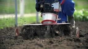 Μηχανοποιημένος καλλιεργητής που αναμιγνύει το φρέσκο χώμα κοντά επάνω σε αργή κίνηση φιλμ μικρού μήκους