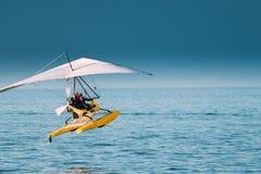 Μηχανοποιημένος κρεμάστε το ανεμοπλάνο με τη μουσουλμανική θάλασσα Frow απογείωσης γυναικών στην ηλιόλουστη θερινή ημέρα στοκ εικόνα