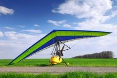 Μηχανοποιημένος κρεμάστε το ανεμοπλάνο πέρα από την πράσινη χλόη στοκ φωτογραφία με δικαίωμα ελεύθερης χρήσης