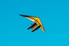 Μηχανοποιημένος κρεμάστε το ανεμοπλάνο που πετά στο μπλε σαφές ηλιόλουστο υπόβαθρο ουρανού στοκ φωτογραφία με δικαίωμα ελεύθερης χρήσης