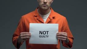 Μη ένοχη φράση στο χαρτόνι στα χέρια του καυκάσιου άνδρα φυλακισμένου, αθώα απόθεμα βίντεο