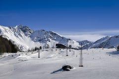 Μη αναγνωρίσιμοι σκιέρ στο χιονοδρομικό κέντρο σε Pila, Valle δ ` Aosta, Ιταλία με chairlift και σκηνικού και αντιγράφων βουνών τ Στοκ Εικόνες