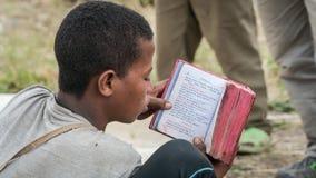 Μη αναγνωρισμένη Βίβλος ανάγνωσης προσκυνητών σε μια από τις παλαιές εκκλησίες βράχου από Lalibela Στοκ Εικόνα