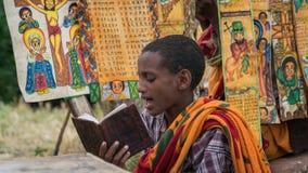 Μη αναγνωρισμένη Βίβλος ανάγνωσης προσκυνητών σε μια από τις παλαιές εκκλησίες βράχου από Lalibela Στοκ Εικόνες