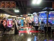 Μη αναγνωρισμένοι άνθρωποι που παίζουν arcade τη μηχανή παιχνιδιών Στοκ φωτογραφία με δικαίωμα ελεύθερης χρήσης