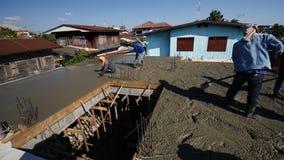Μη αναγνωρισμένοι εργαζόμενοι που χύνουν και που ισοπεδώνουν το υγρό τσιμέντο στην εργασία πατωμάτων στο εργοτάξιο οικοδομής φιλμ μικρού μήκους