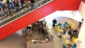Μη αναγνωρισμένος άνθρωποι ή πελάτης που που οδηγούν μια κυλιόμενη σκάλα και που περπατούν στη λεωφόρο αγορών απόθεμα βίντεο