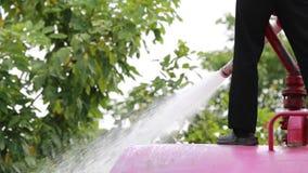 Μη αναγνωρισμένος ασιατικός εργαζόμενος που χρησιμοποιεί έναν ισχυρό ψεκαστήρα μανικών από ένα φορτηγό βυτιοφόρων για να πλύνει τ απόθεμα βίντεο