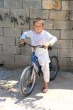 Μη αναγνωρισμένο αφγανικό αγόρι με το ποδήλατο που στέκεται και που θέτει μπροστά από το σπίτι του Στοκ φωτογραφία με δικαίωμα ελεύθερης χρήσης