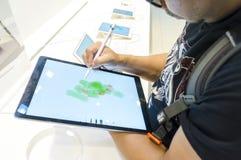 Μη αναγνωρισμένο σκίτσο ατόμων με τη χρησιμοποίηση του μολυβιού της Apple με τη νέα Apple Ipad υπέρ Στοκ Εικόνες