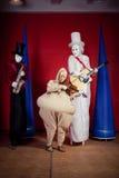 Μη κατανοητοί μουσικοί πλασμάτων freaks Τρία κορίτσια ή αγόρια με τη μάσκα προσώπου αποκριών στο κόκκινο υπόβαθρο Στοκ εικόνες με δικαίωμα ελεύθερης χρήσης