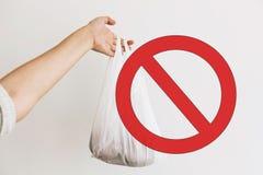 Μιάς χρήσεως πλαστικό απαγόρευσης, σημάδι στάσεων Γυναίκα που κρατά τα διαθέσιμα παντοπωλεία χεριών στην πλαστική τσάντα πολυαιθυ στοκ εικόνες