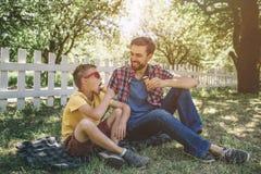 Μια άλλη δροσερή εικόνα της συνεδρίασης ενηλίκων και παιδιών μαζί και εξετάζοντας ο ένας τον άλλον Τρώνε το παγωτό Μικρό αγόρι Στοκ Εικόνα