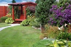 Μια άνετη γωνία του κήπου με έναν πάγκο, έναν χορτοτάπητα και το άνθισμα cle στοκ φωτογραφίες