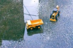 Μια άποψη άνωθεν ενός φορτηγού και ενός παιχνιδιού λαογραφίας στο πάτωμα τσιμέντου μετά από τη βροχή άνοιξη Στοκ Εικόνες