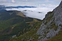 Μια άποψη από μια κλίση στη σειρά βουνών Komovi στα λιβάδια και τα δάση κατωτέρω στοκ φωτογραφία