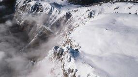 Μια άποψη από τον αέρα πέρα από τους απότομους βράχους που καλύπτονται με το χιόνι μια ηλιόλουστη ημέρα στοκ εικόνες με δικαίωμα ελεύθερης χρήσης