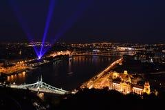 Μια άποψη νύχτας πέρα από την πόλη της Βουδαπέστης με το τουριστικό αξιοθέατο γεφυρών ελευθερίας στο πλαίσιο Στοκ φωτογραφία με δικαίωμα ελεύθερης χρήσης