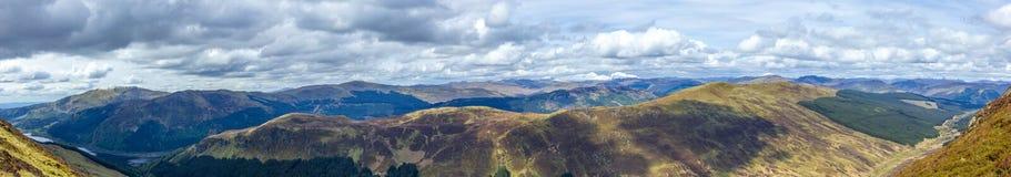 Μια άποψη πανοράματος μιας σκωτσέζικης σειράς βουνών με τις λίμνες, δάσος πεύκων κάτω από έναν μεγαλοπρεπή νεφελώδη άσπρο ουρανό στοκ εικόνα με δικαίωμα ελεύθερης χρήσης