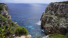 Μια άποψη της μπλε θάλασσας με τους βράχους σε Minorca Ισπανία Στοκ Εικόνες