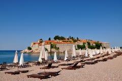 Μια άποψη του νησιού Sveti Stefan μια θερινή ημέρα με τις ομπρέλες παραλιών και τους αργοσχόλους, Μαυροβούνιο Στοκ Εικόνες